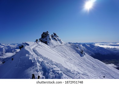 View of the summit of Treble Cone on a perfect bluebird powder day. Deep hiking footprints in the snow