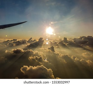 View of the sun rays illuminating the dark clouds from a plane