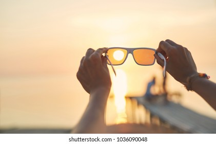 view of the sun, sea and sky through sunglasses at sunset