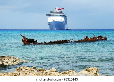 The view of a sunken ship with a cruise liner in a background on Grand Cayman island (Cayman Islands).