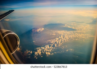 View of the sunrise and the clouds from within, out of the plane