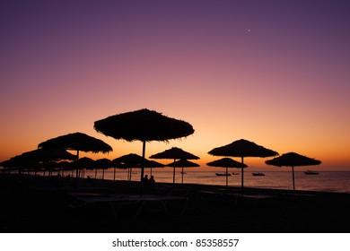 The view of sunrise at Kamari Beach in Santorini Island, Greece.