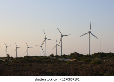 View at sunset of the beautiful white sandstone cliffs of Bozcaada island in Turkey with wind energy turbines in the background.
