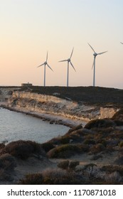View at sunset of the beautiful white sandstone cliffs and wind energy turbines of Bozcaada island in Turkey.