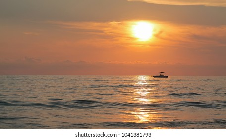View of sunset and a lonely boat on the sea