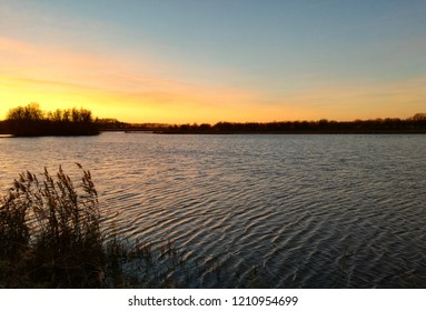 View of a sunset over a lake from a hide in the Oostvaardersplassen in Flevoland on a autumn day, in The Netherlands