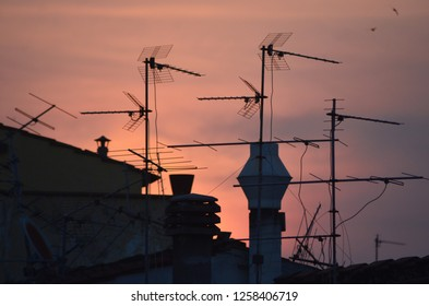 A view at sunset over a roofline of chimneys and television antenna.