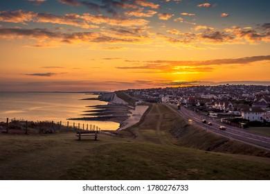 Der Blick auf den Sonnenuntergang von Saltdean im Sommer Richtung Brighton, Großbritannien