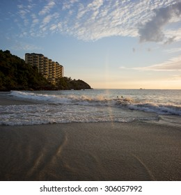 View of surf on the beach at sunsest with apartment buildings in background, Ixtapa, Zihuatanejo, Guerrero, Mexico