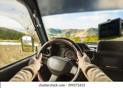 view from SUV car inside with part of interior and mirror with driver male hand on the steering wheel on danger straight hill road during sunny day with snowy mountains in background