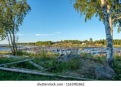 View from the Swedish side of Kukkola rapids across Torne river towards Finland on a summer day in August 2018. Kukkola rapids has been a fishing site since medieval times.
