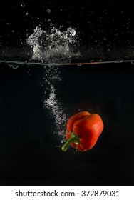 View of sweet pepper dropping into water on black background.