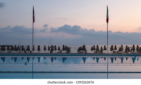 view of a swimming pool by a sea on a summer's evening
