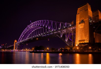 View of Sydney, Australia. View across harbour from south to north. Vivid orange and purple lights reflected in bay waters. Sydney Harbour Bridge, New South Wales.