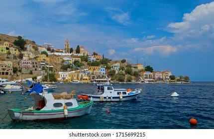 View of Symi Harbour with fishing boats in the foreground and Annunciation Church in the background.