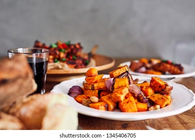 View of table served with traditional British Sunday roast dinner, featuring roasted chicken, squash and sweet potatoes