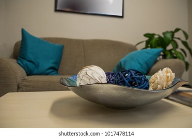 View of table top of an office waiting room. Image presents decorative on the foreground and a brown couch in the background