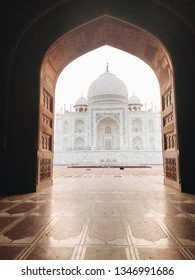 View of the Taj Mahal through a large pink Archway at sunrise, Agra, India