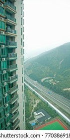 view from a tall apartment building many stories up looking at highway