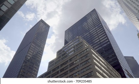 View of tall skyscrapers in large urban city looking straight up against cloud sky background day time exterior from street level