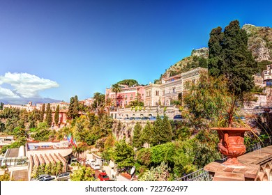 View of Taormina - famous resort in Sicily, Italia. With flower pot against blue sky. Beautiful travel landscape.