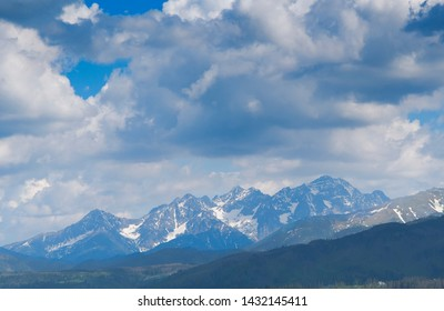 View of Tatra mounains.Tatra mountains in the morning. Beautiful green valley at snowy mountains foothills.