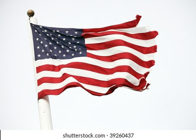 View of tattered American flag on flagpole blowing in the wind.