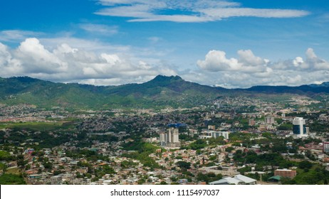 view of Tegucigalpa city in Honduras, houses and buildings in the city, mountains in the background. photo taken on a partly cloudy summer day.