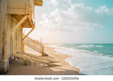 View of Tel Baruch beach in Tel Aviv, Israel. Baywatch cabin against rays of lights and mediterranean horizon.