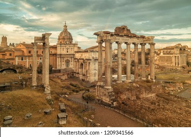 View of the temple of Saturn in Roman forum, Italy. Ruins of Septimius Severus Arch and Saturn Temple. Rainbow over the Roman forum. Rome architecture and landmark.