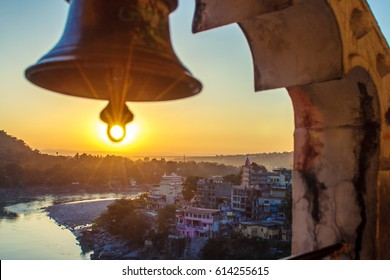 View from the temple under huge bell on River Ganga and Lakshman Jhula bridge at sunset. Rishikesh. India
