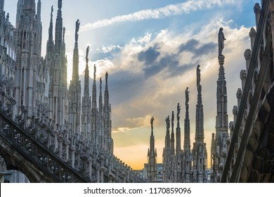 View of terrace and statues on the spires at the rooftop of Duomo di Milano, catholic church, in Milan, Italy with twilight and cloudy sky background.