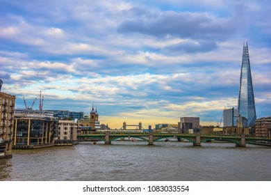 View of the Thames River at sunset in London, England. The London Tower bridge can be seen in the background.