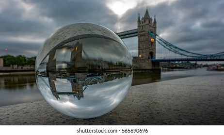View of the Thames river and Tower Bridge through a crystal ball on a early cloudy morning in London