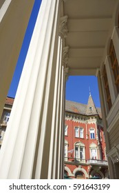 View of the theater building in Subotica, Serbia. Pillar in the building, detail. Red building in the background