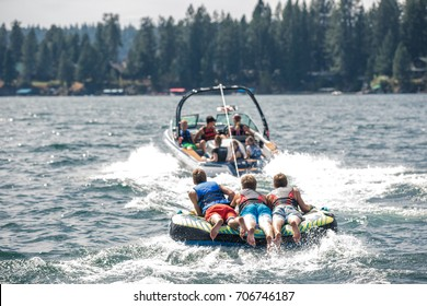 View of the thee guys riding on a mat following a boat
