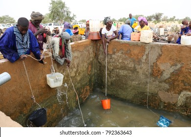 View of thirsty people drawing water in a reservoir with buckets and ropes. The scene takes place in North Senegal in a village of Louga region. The picture has been taken on 13rd november 2015.