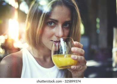 View though the window of a young gorgeous woman enjoying a natural fruit juice and looking at you, caucasian blonde hair female standing indoors and drinking freshly juiced beverage of orange