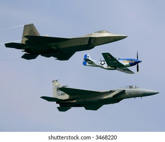 A view of three different types of military fighter aircraft from three different eras.  A P51 propeller aircraft, a modern F15 jet fighter and the futuristic F22.