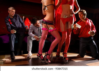 View of three men offering money to strippers on stage