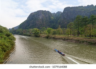 View of three small boats on the Nam Song River and limestone karst mountains near the Tham Chang (or Jang or Jung) Cave in Vang Vieng, Laos.