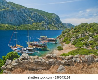 view of three tourist boats at Camellia island in Aegean Sea from medieval wall ruins with mountains at background, Marmaris Turkey