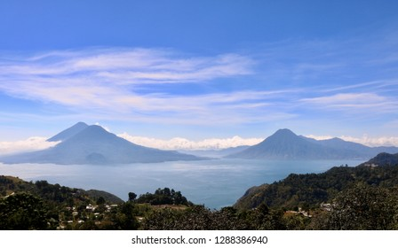 View of three volcanoes (Volcán San Pedro, Volcán Tollmán, and Volcán Atitlán) standing over Lake Atitlán in Guatemala