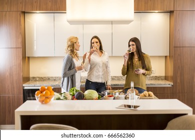 View at three women friends toasting white wine in modern kitchen