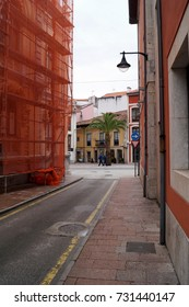 View through an alley to a T-junction and a palm tree, two pedestrians passing by; Llanes, Asturias, Spain, 04/06/2017