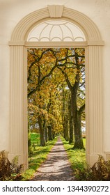 view through arched door, autumnal walkway along bright oak tree alley.