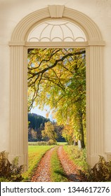 view through arched door, autumnal walkway along the edge of the wood, with oak trees.