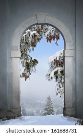 view through arched gate to winter landscape