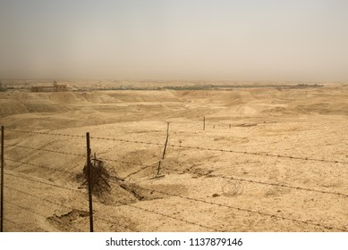 View through barbed wire on the road to  the River Jordan, where Jesus was baptised, over the dangerous no man's land desert which is a minefield left over from the wars between Israel and Jordan