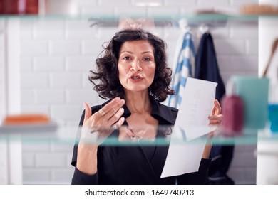 View Through Bathroom Cabinet Of Mature Businesswoman Practising Presentation